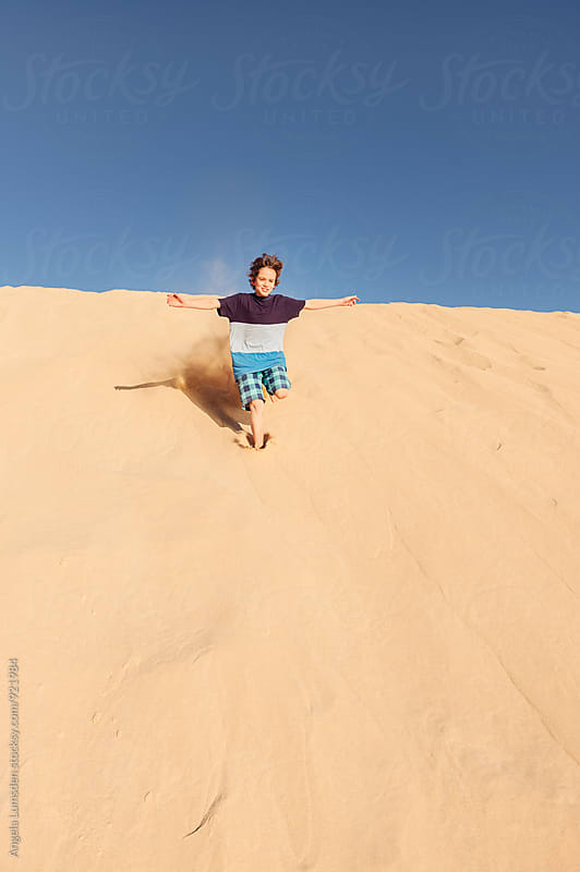 Boy with outstretched arms and a big smile running down a sand dune by Angela Lumsden for Stocksy United