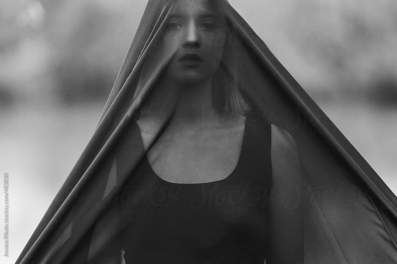 Young woman hiding behind a veil by Jovana Rikalo for Stocksy United
