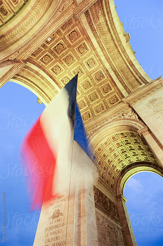 French tricolour flag flying at dusk, Arc de Triomphe, Paris, France, Europe by Gavin Hellier for Stocksy United