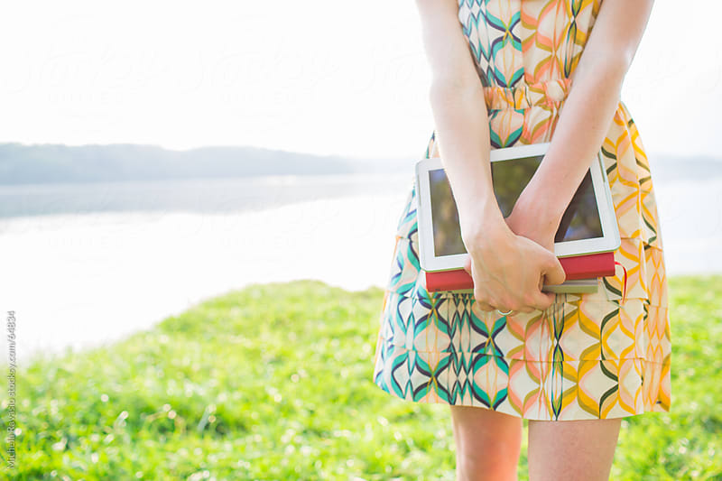 Young woman holding digital tablet and books by michela ravasio for Stocksy United