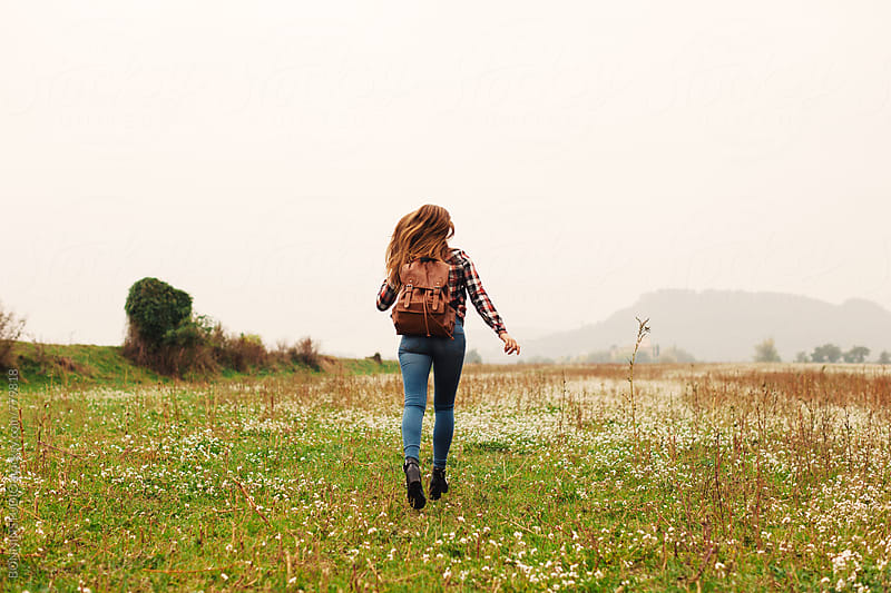 Back view of a 14 years old girl running in a field. by BONNINSTUDIO for Stocksy United