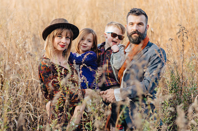Beautiful and trendy family standing in a field by Jakob for Stocksy United