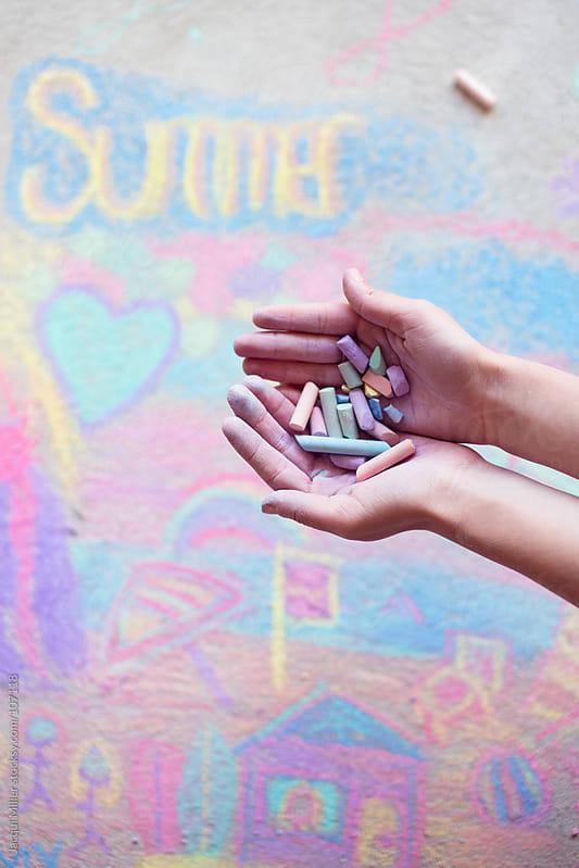 A handful of chalk held above a colourful pavement chalk drawing by Jacqui Miller for Stocksy United
