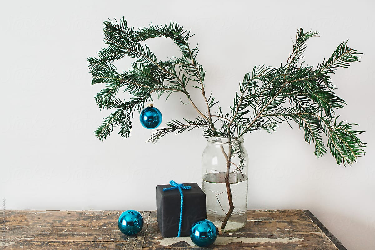 simple evergreen pine branch in glass jar decorated for holidays