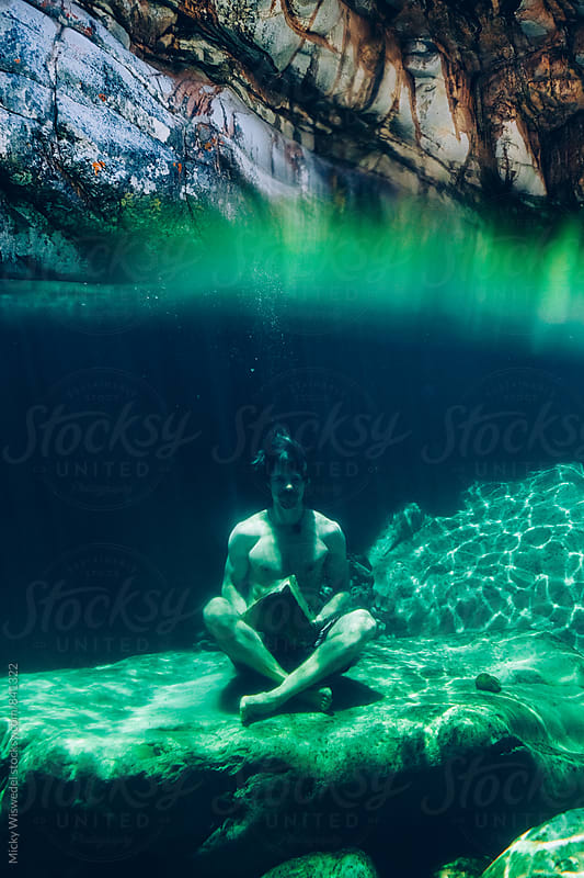 split perspective of a man holding a rock underwater meditating in a mountain river rock pool by Micky Wiswedel for Stocksy United