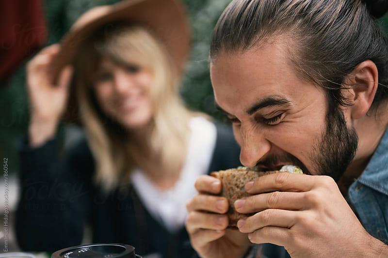 Man taking bite of delicious sandwich by Emmanuel Hidalgo for Stocksy United