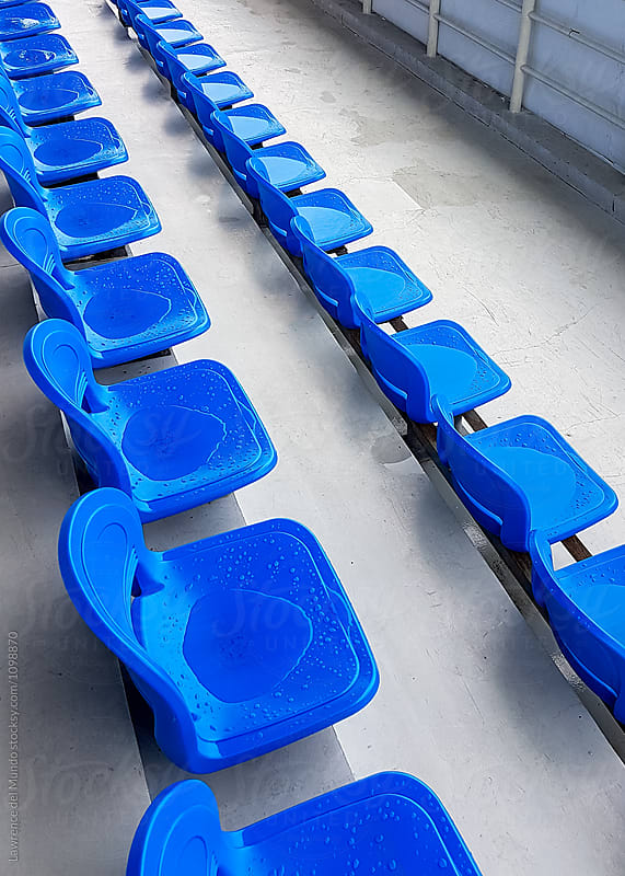 Wet, empty seats in the bleacher section of a stadium.  by Lawrence del Mundo for Stocksy United
