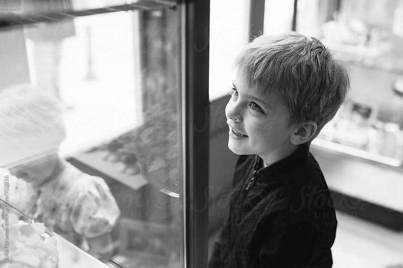 Children looking in glass cabinets in a patisserie. by Julia Forsman for Stocksy United