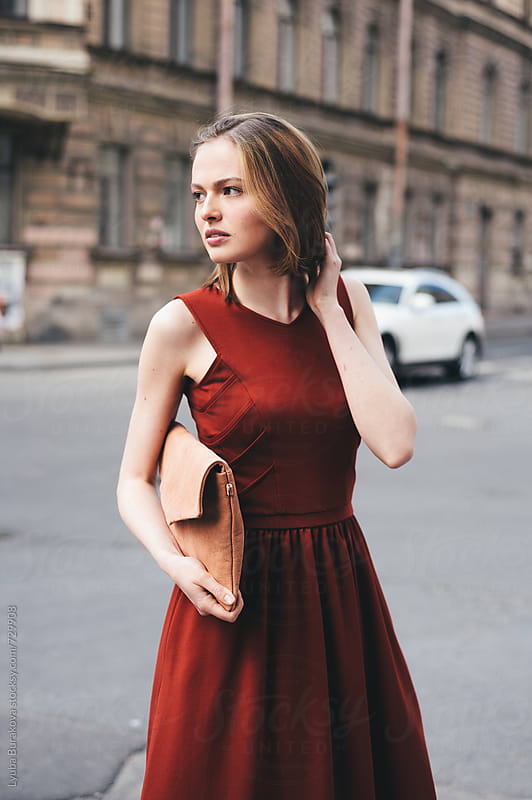 Woman standing on the street with a clutch by Lyuba Burakova for Stocksy United