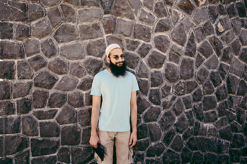 Bearded man besides wall by Murtaza Daud for Stocksy United