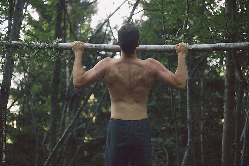 Young man doing chin-ups on a log in the nature by Miquel Llonch for Stocksy United