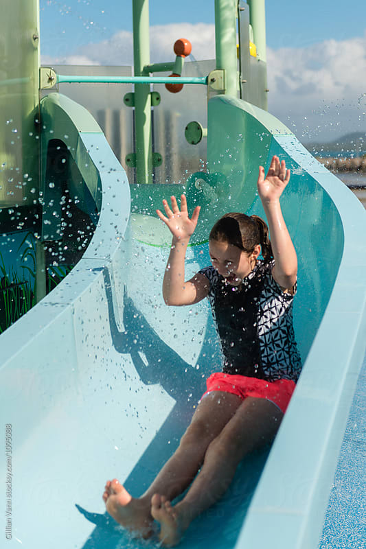 girl at a waterpark being splashed with water on a slide by Gillian Vann for Stocksy United