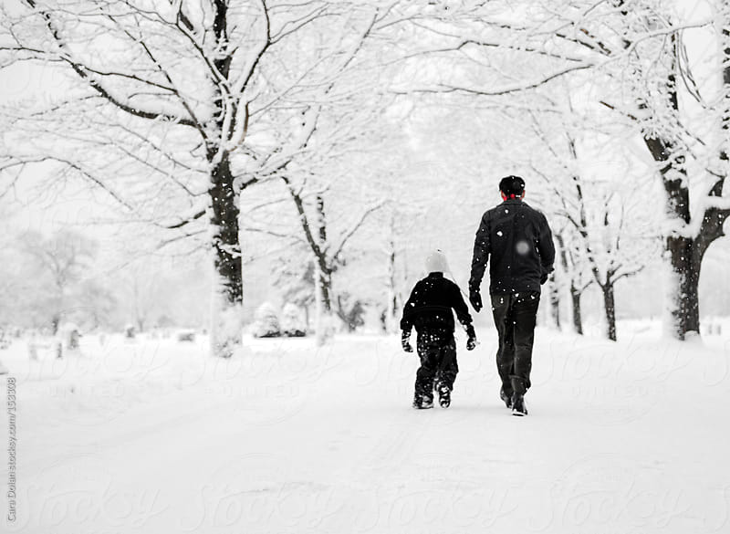 Boy and his dad walk down a tree-lined street during a big snow by Cara Dolan for Stocksy United
