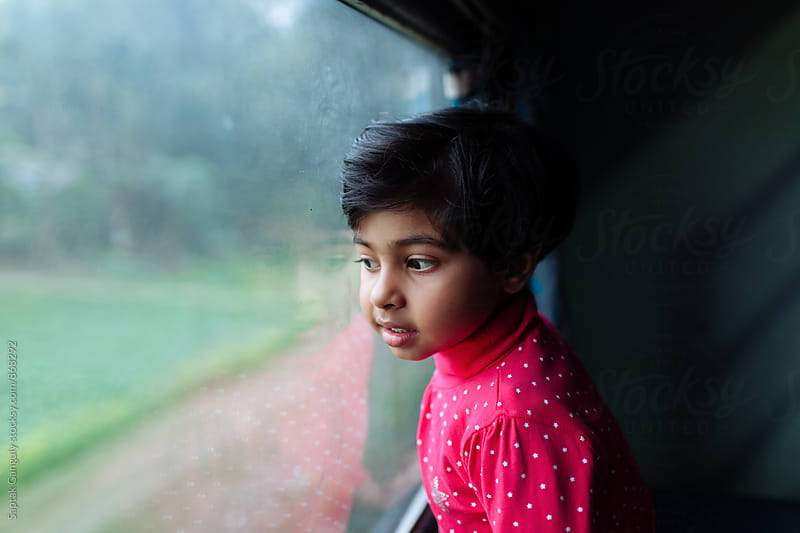 Child looking through a train window by Saptak Ganguly for Stocksy United
