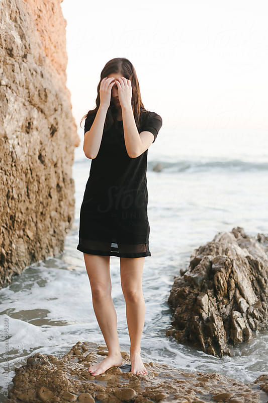 Young Woman Fixes her Hair On Beach Standing on a Rock by Caleb Thal for Stocksy United