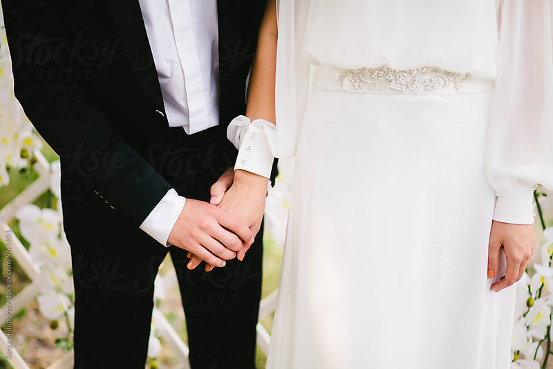 Bride and groom holding hands by Sergey Filimonov for Stocksy United