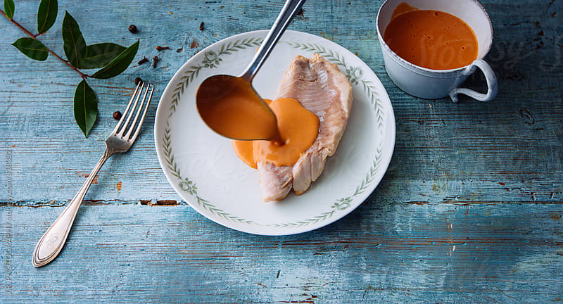 Pouring sauce on cod fillet by J.R. PHOTOGRAPHY for Stocksy United