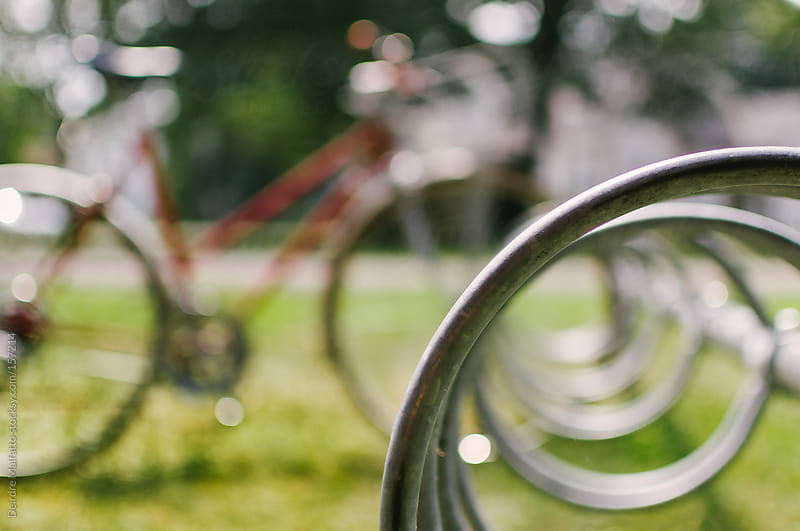 bicycle parked in circular bike rack by Deirdre Malfatto for Stocksy United