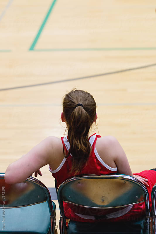female basketball player sits in chair watching game  by Tana Teel for Stocksy United