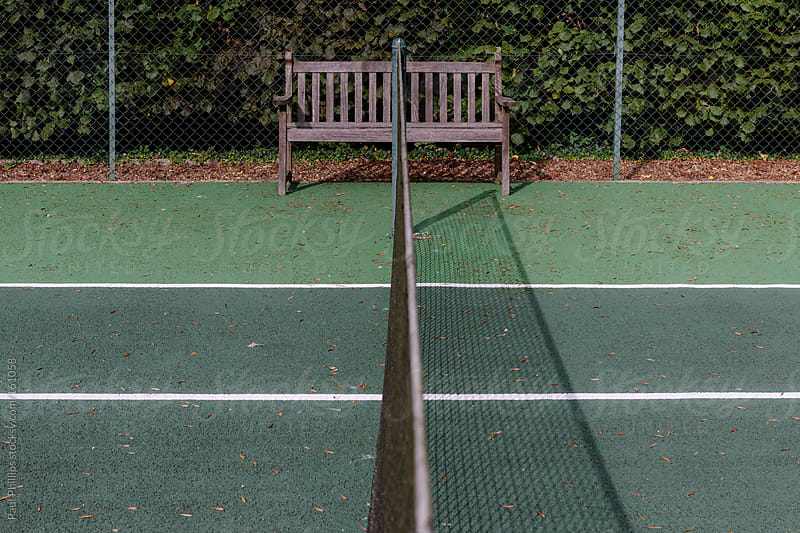 Bench at the end of the centre line of a tennis court by Paul Phillips for Stocksy United