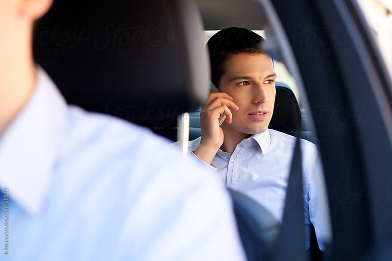 Businessman sitting in a backseat of the car and talking on the phone.  by Mosuno for Stocksy United