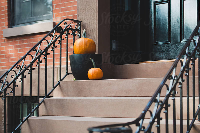 Pumpkins on steps of brownstone apartment building by Lauren Naefe for Stocksy United