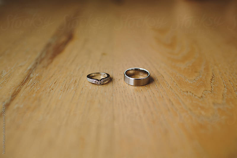 wedding rings on hard wood floor by Nicole Mason for Stocksy United
