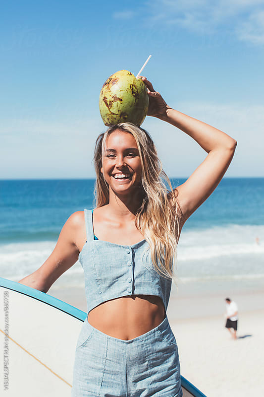 Portrait of Young Blond Laughing Girl Holding Fresh Coconut on Head by Julien L. Balmer for Stocksy United