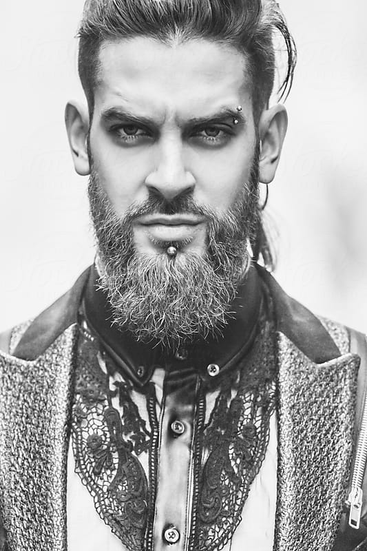 portrait of a stylish handsome young man with a beard and piercing in a suit by Igor Madjinca for Stocksy United