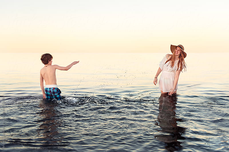 Splash - boy and girl playing together in calm water after sunset by Angela Lumsden for Stocksy United