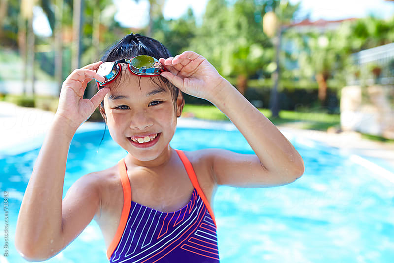 lovely little asian girl smile at camera by the swimming pool by Bo Bo for Stocksy United