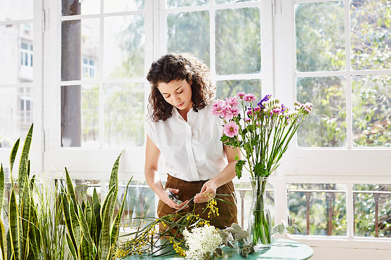 Woman Trimming Plants By Flower Vase At Home by ALTO IMAGES for Stocksy United