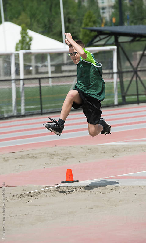 Boy Doing Long Jump At Track Meet by Ronnie Comeau for Stocksy United