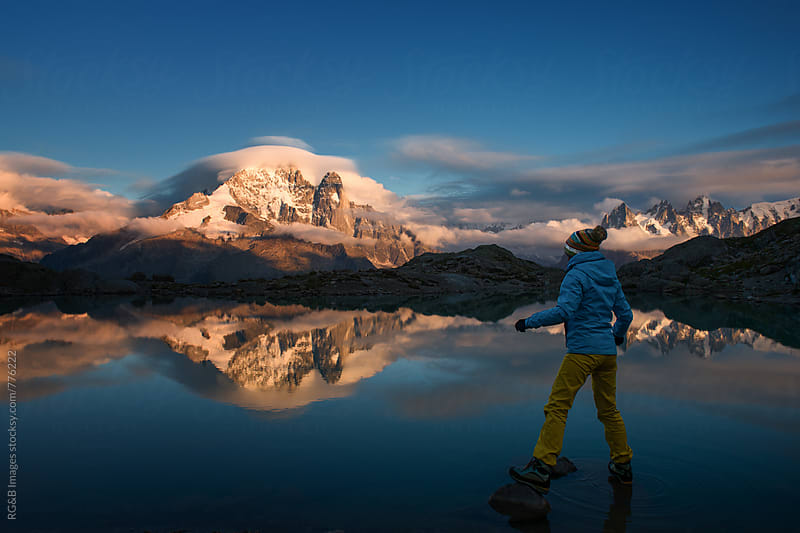 Woman standing on rocks at sunset, Lake Blanc, Alps by RG&B Images for Stocksy United