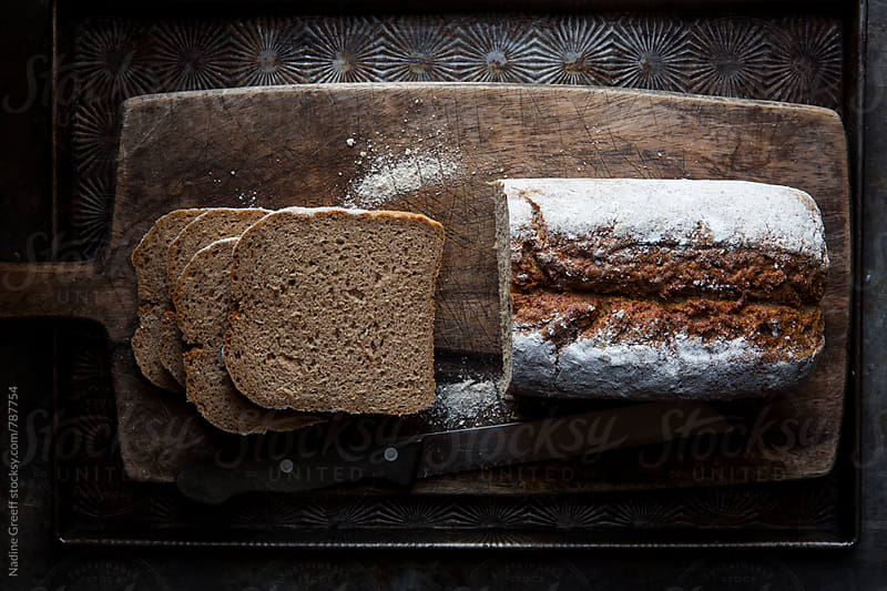 Top view of rye bread loaf with slices on bread board by Nadine Greeff for Stocksy United
