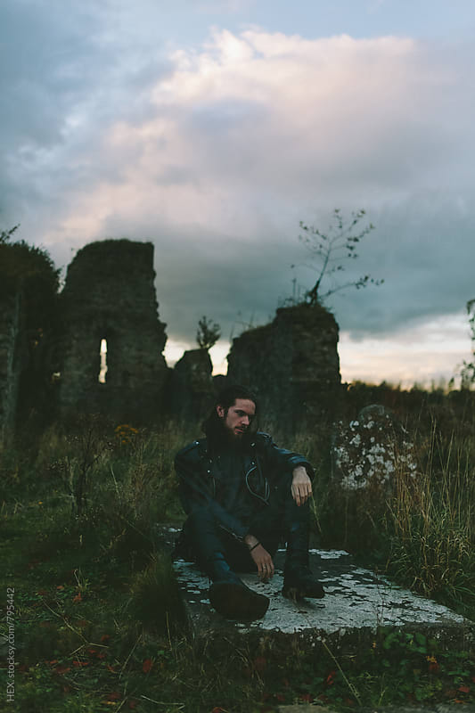 Man Sitting on a Grave in the Cemitery by Mattia Pelizzari for Stocksy United