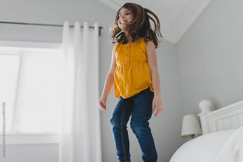 Happy, smiling girl jumping on bed, movement by Amanda Worrall for Stocksy United