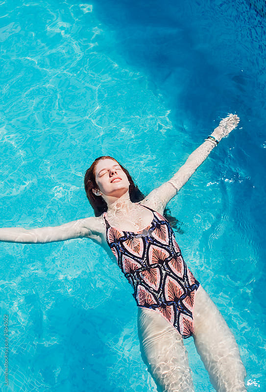 Woman Floating in the Swimming Pool by Lumina for Stocksy United