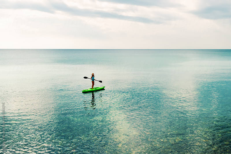 tween girl standing on a sea kayak, having fun on summer holidays by Gillian Vann for Stocksy United