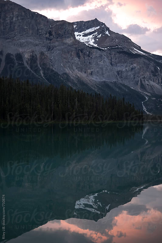 A mountain is reflected in a lake at sunset by Riley Joseph for Stocksy United