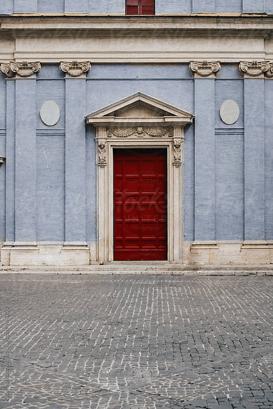 Red Door on a Blue Pastel Building by Katarina Radovic for Stocksy United