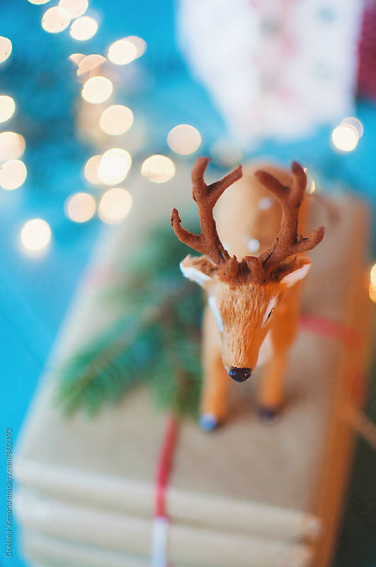 A toy deer on top of a stack of christmas presents by Chelsea Victoria for Stocksy United