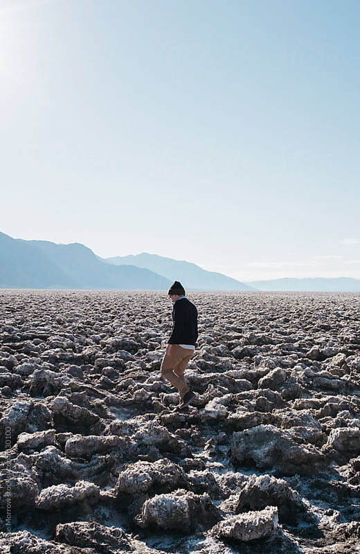 young male walking through treacherous salt flat landscape with mountains in background by Jesse Morrow for Stocksy United