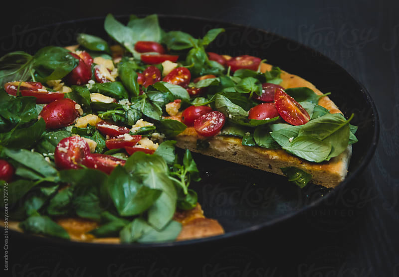 Vegetable pizza without one slice by Leandro Crespi for Stocksy United