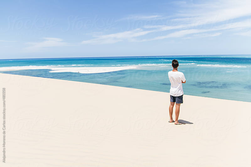 Young man wearing swimsuit looking at the ocean on an exotic tropical beach with turquoise water by Alejandro Moreno de Carlos for Stocksy United
