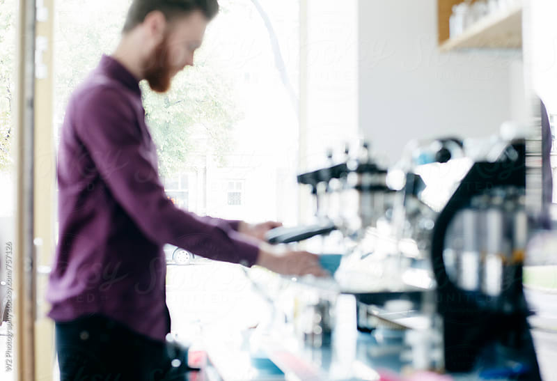 Out of focus man making coffee in a cafe. by W2 Photography for Stocksy United