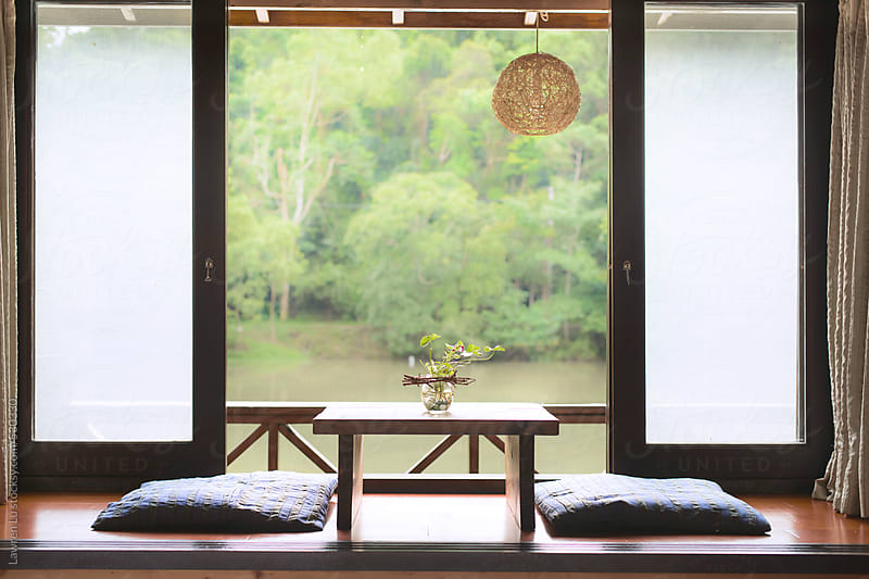 Interior of a wooden house with sliding screens opened to overlook a tranquil lake and green trees, Taipei, Taiwan by Lawren Lu for Stocksy United