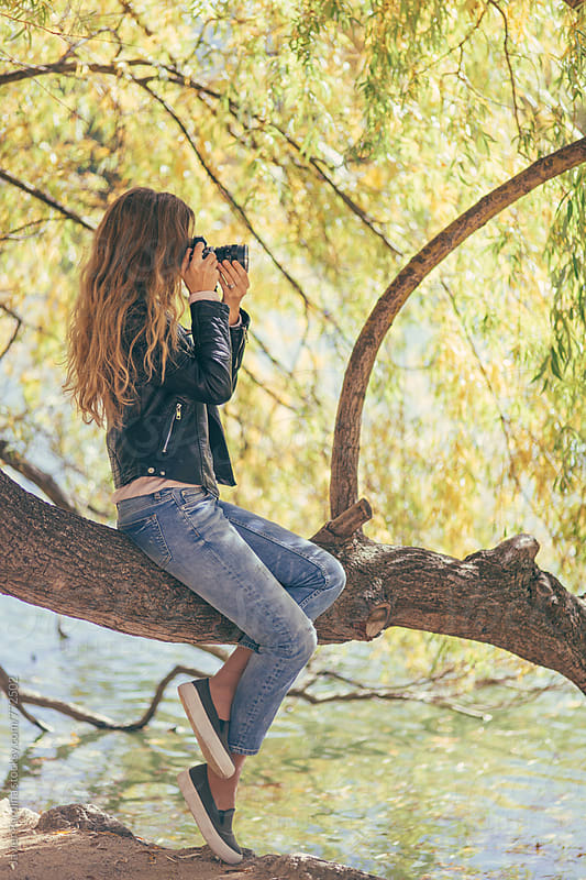 woman taking photos on the tree by Javier Pardina for Stocksy United