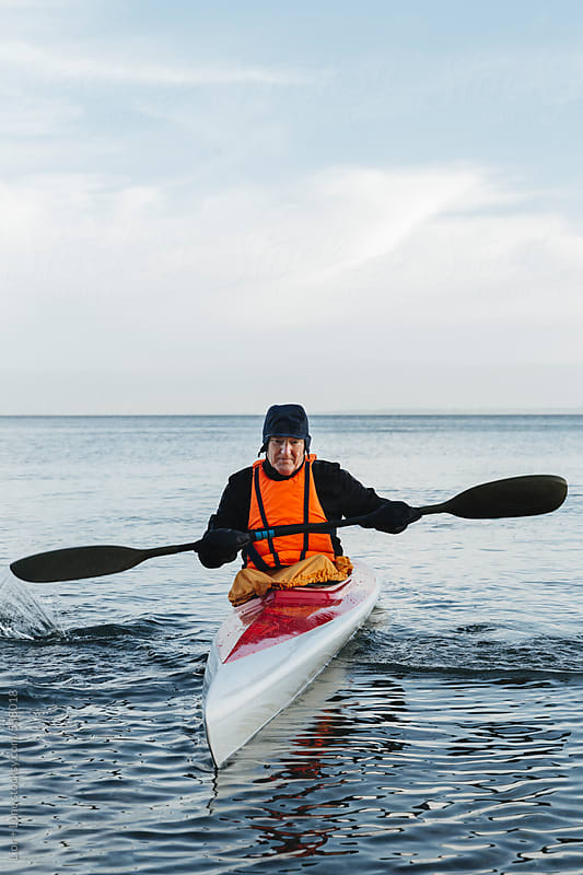 Senior man using paddle to balance kayak by Lior + Lone for Stocksy United