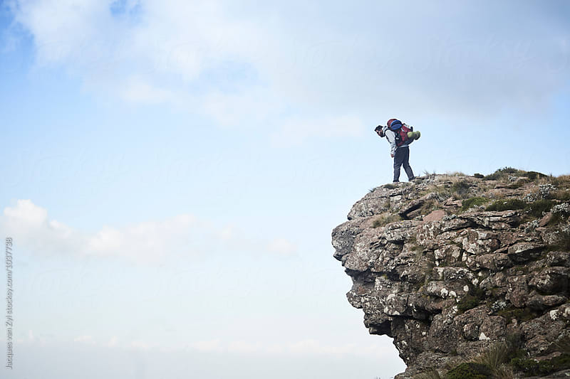 A hiker with his back pack looking over and down a rock cliff edge. by Jacques van Zyl for Stocksy United